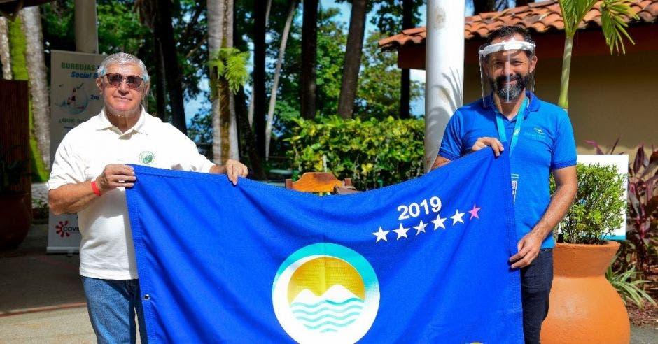 Dos hombres sostienen una bandera azul
