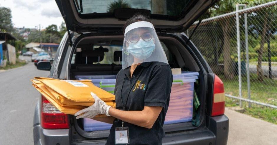Una mujer con mascarilla sostiene unos documentos