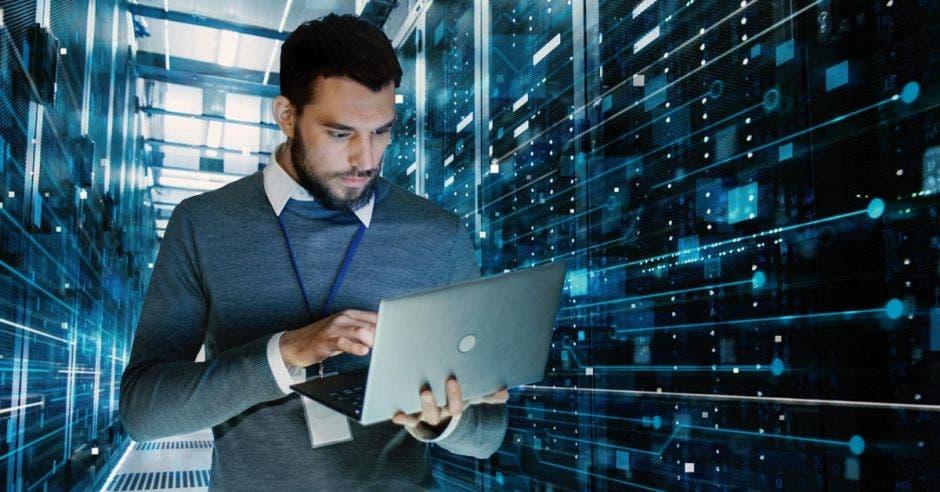Muchacho revisa su computadora en una sala de servidores