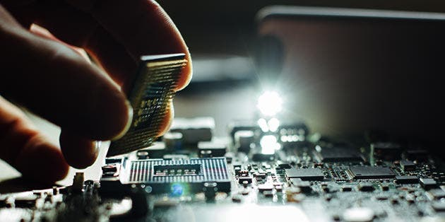 Acercamiento de una mano instalando un chip de computadora