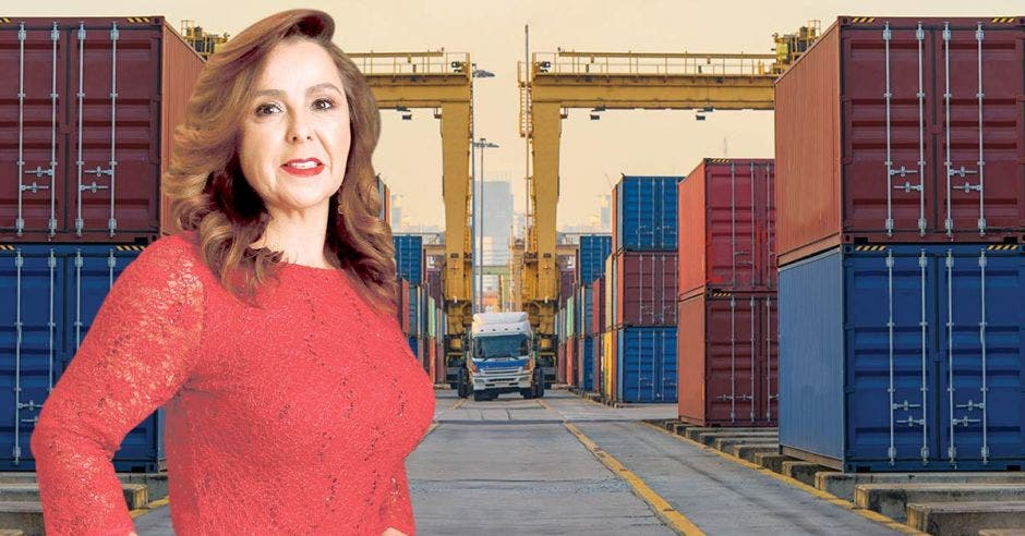 Mujer de vestido rojo posa frente a contenedores