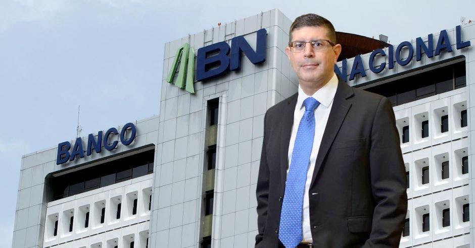 Hombre de traje frente a fachada del Banco Nacional