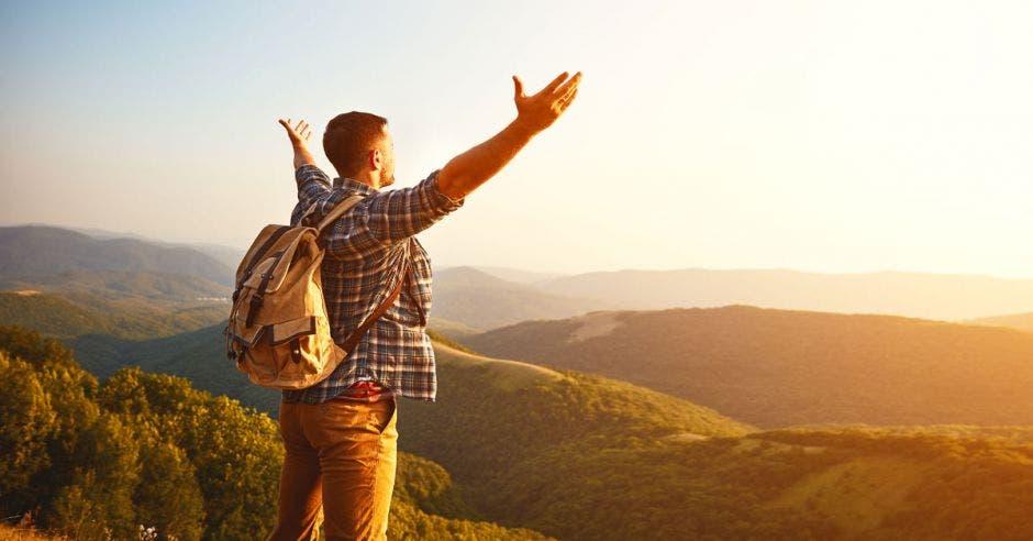 Un turista con las manos abiertas al horizonte