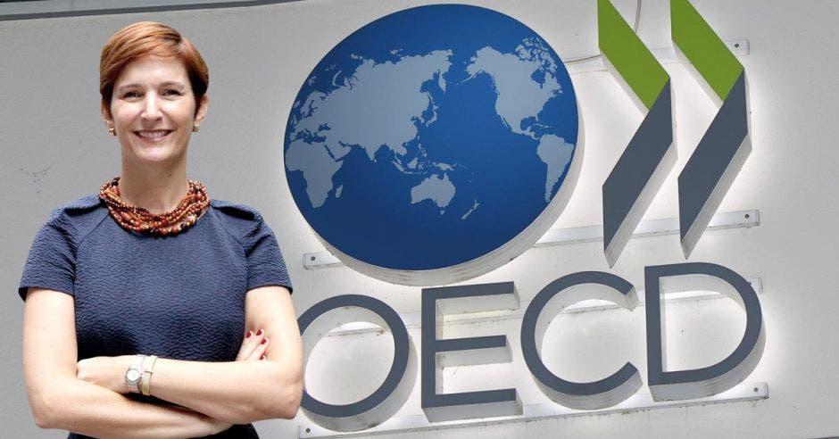 Mujer sonriente frente a logo de la OCDE