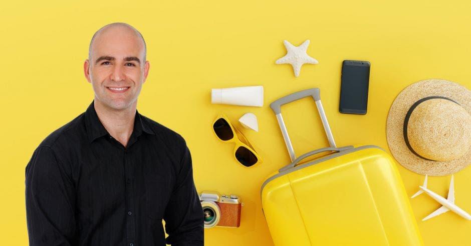 Un hombre calvo de mediana edad sobre un fondo amarillo de valijas, conchas y anteojos de sol