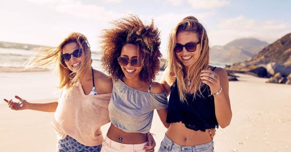 Tres mujeres sonrientes disfrutan de una caminata en la playa