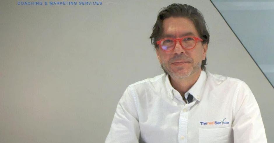 Un hombre mayor con camisa blanca y anteojos de aro rojo