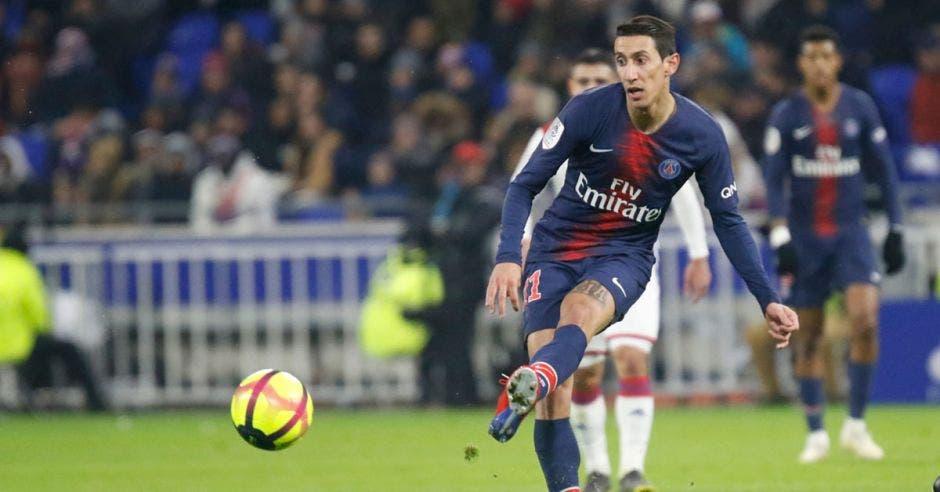 Un jugador de fútbol con uniforme azul pateando el balón con su pierna izquierda