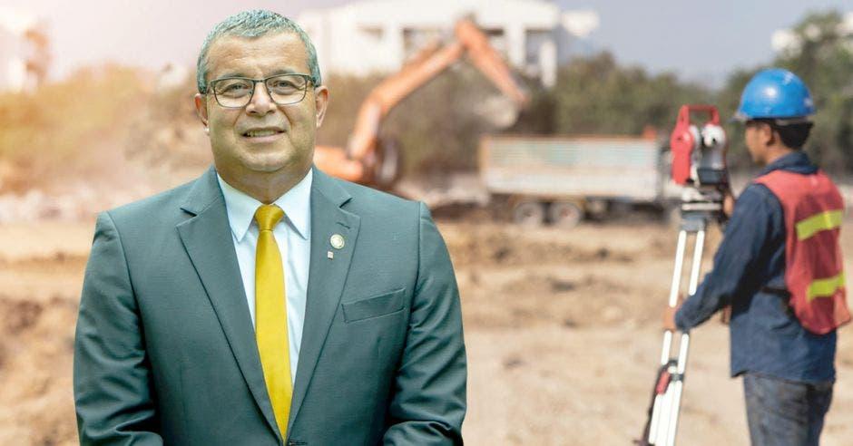 Un hombre de saco gris y corbata amarilla posa sobre un fondo de construcción