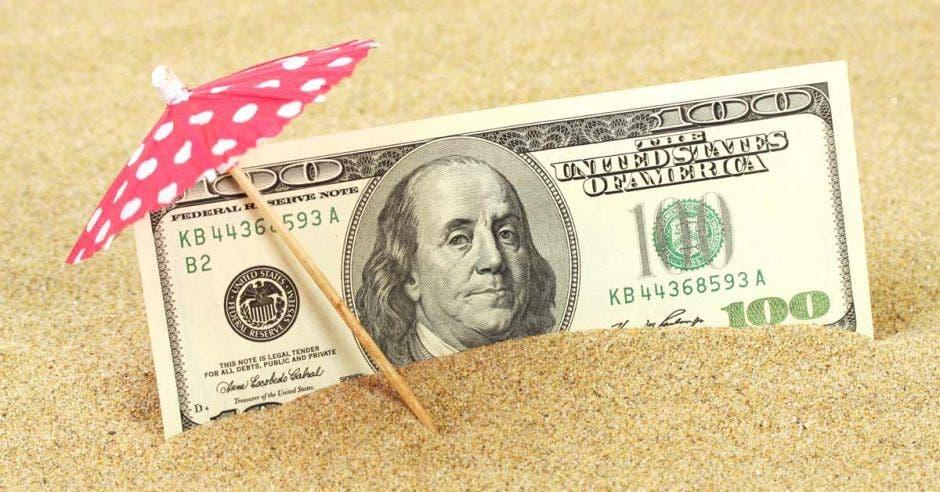 Un dólar en la arena bajo una sombrilla rosada