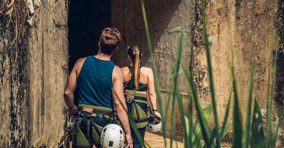 Dos personas en ropa deportiva con un casco suben por una escalera de piedra