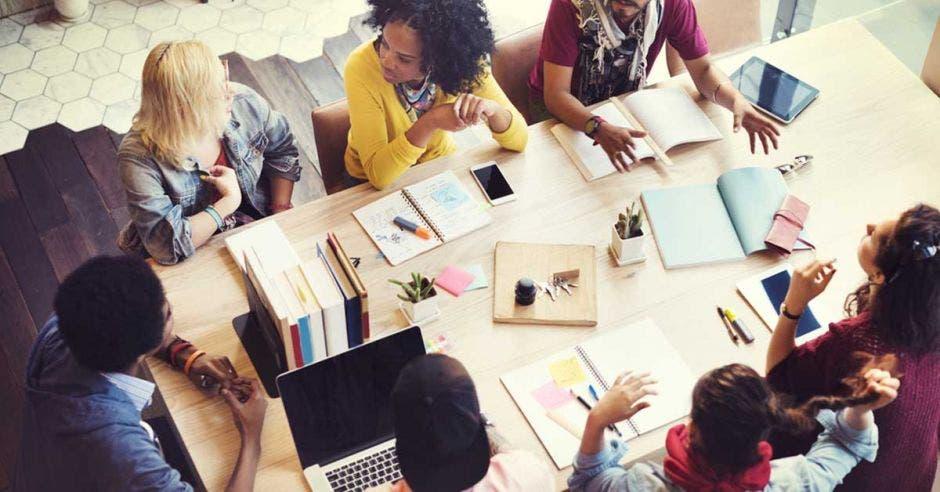 Personas sentadas en una mesa discutiendo ideas