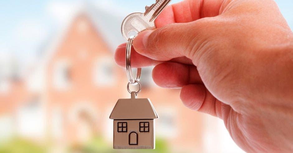 Persona sostiene llaves con llavero en forma de casa