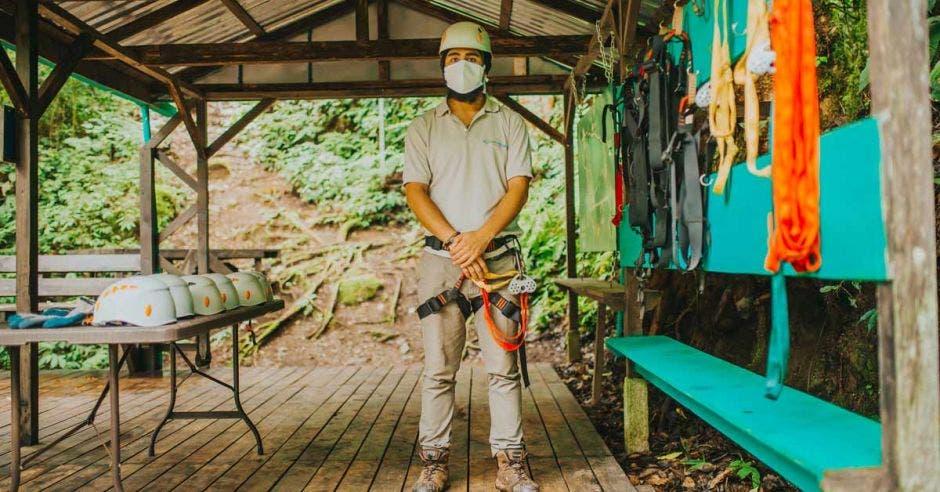 Un hombre con mascarilla equipado con implementos para hacer canopy