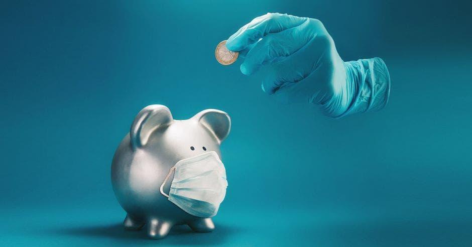Guante con moneda echando a alcancía de cerdo con mascarilla