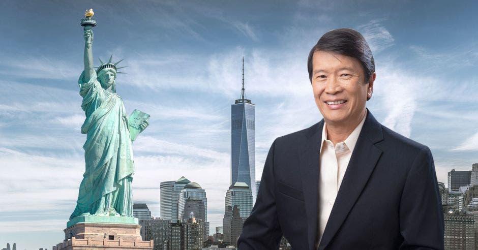 Un hombre asiático sonríe junto a una imagen de la estatua de la libertad