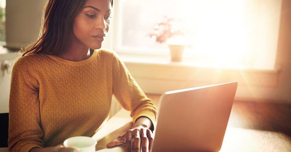 Una mujer afrodescendiente frente a una computadora color gris