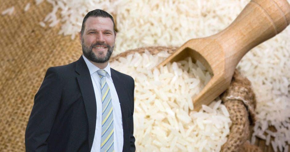 Un hombre con saco y corbata junto a un saco de arroz