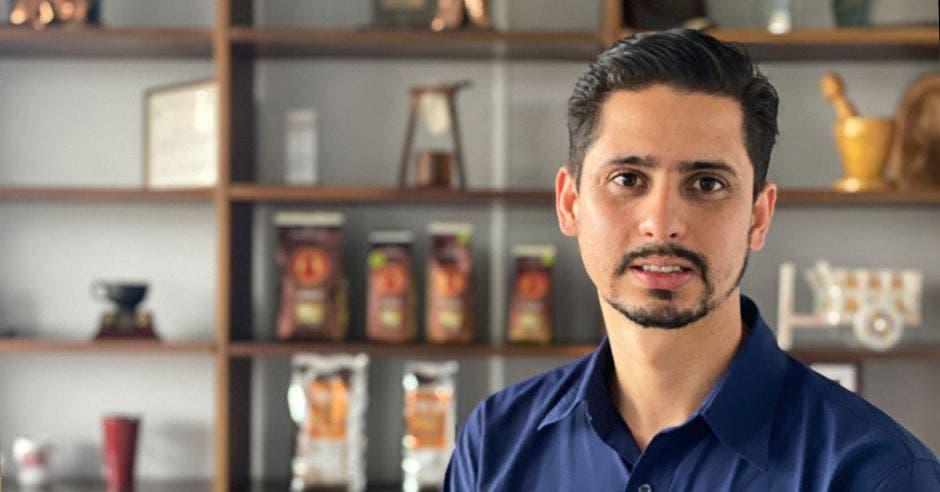 Un hombre sonríe en medio de estantes con bolsas de café