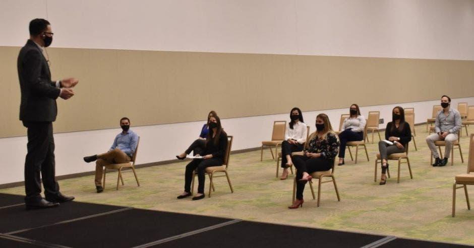 UN hombre con mascarilla habla frente a un auditorio