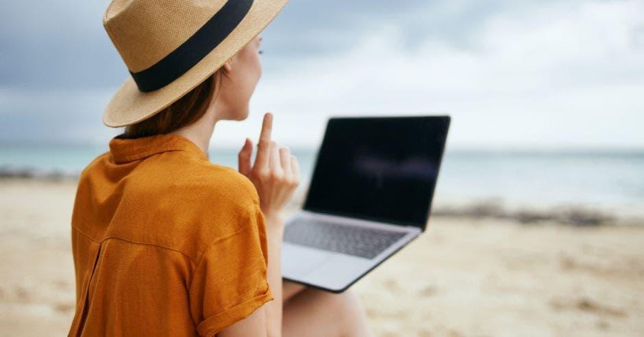 Una mujer disfruta de una vista en la playa con su computadora
