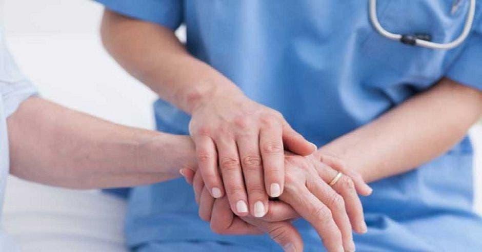 Una enfermera agarrando una mano