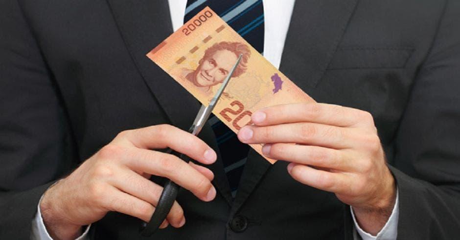 Un hombre con un billete en la mano y una tijera