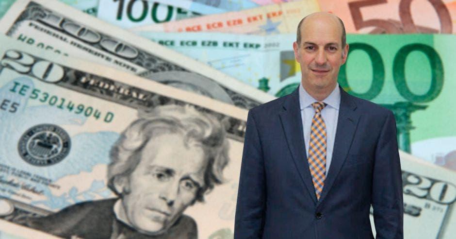 Hombre de traje frente a billetes.