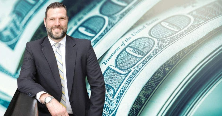 Persona de traje frente a arte de dólar