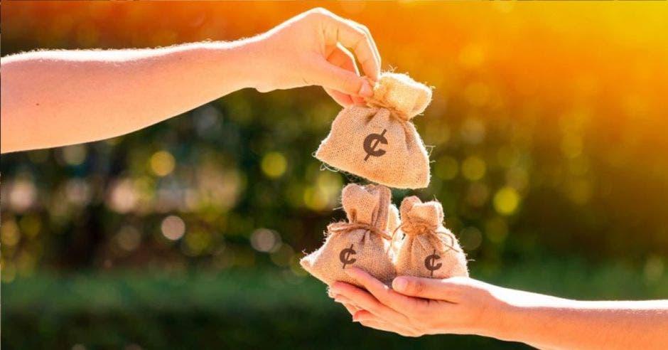 Personas dándose bolsas de dinero