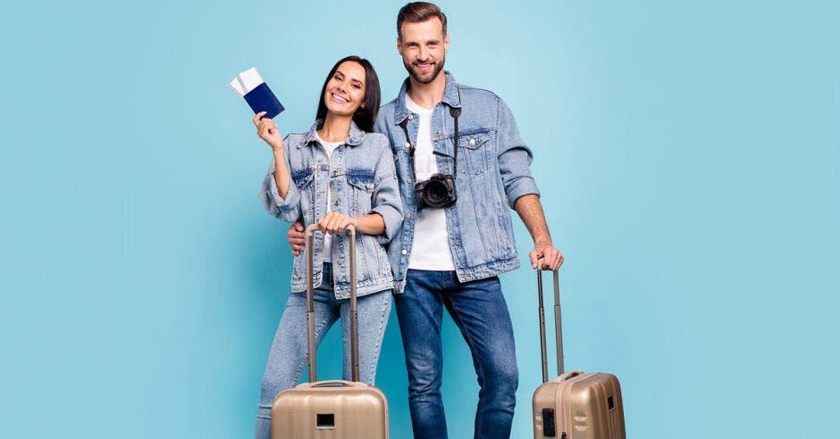 Dos turistas con dos valijas sobre un fondo celeste