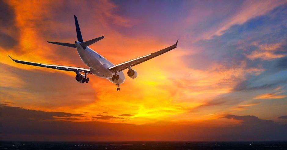 Un avión sobre un atardecer