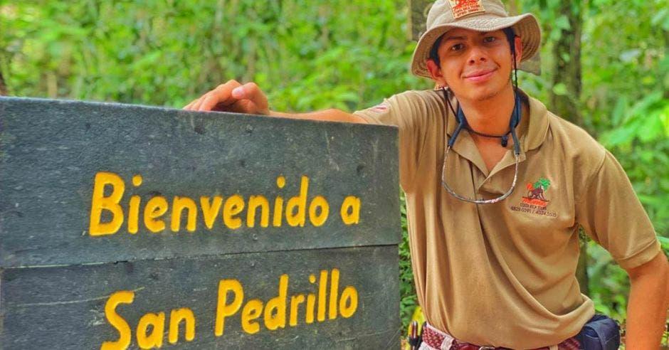 Un joven se apoya sobre un letrero que dice Bienvenido a San Pedrillo