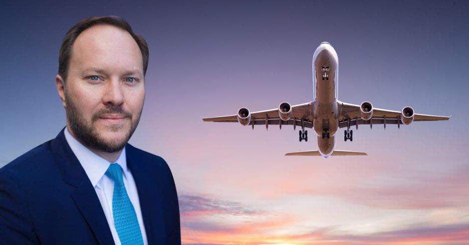 Un hombre calvo de ojos azules sobre el fondo de un avión despegando al atardecer