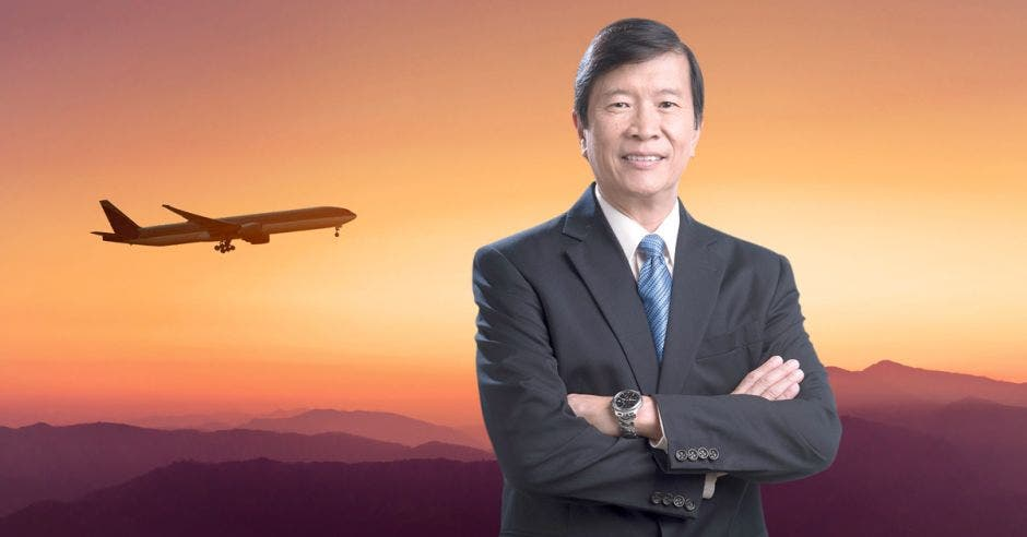 Un hombre con saco oscuro y corbata azul sobre un fondo de avión
