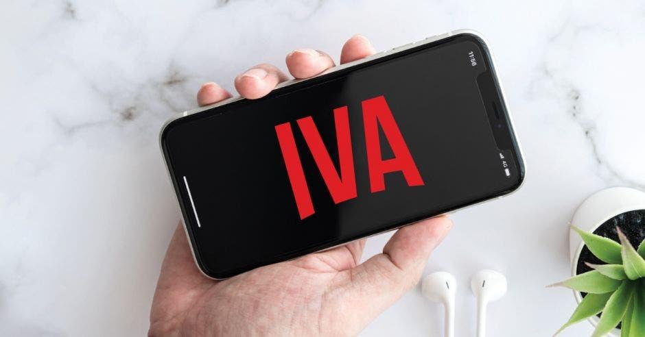 Una persona sostiene un celular que dice la palabra IVA