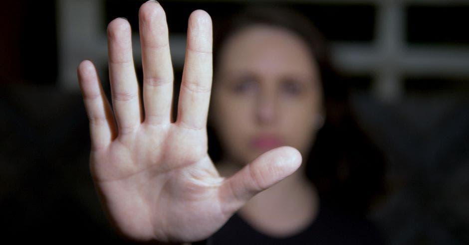Vemos una mujer con la mano enfrente.