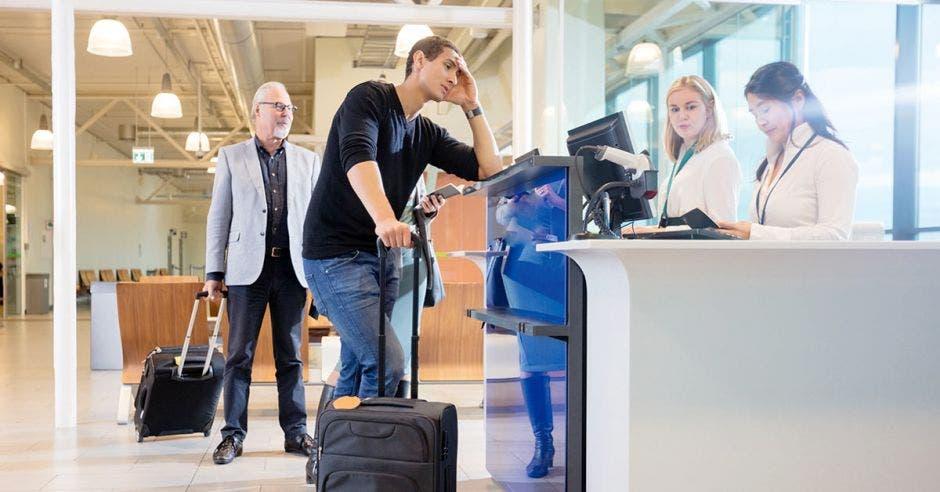 Un hombre se apoya sobre el mostrador de un aeropuerto