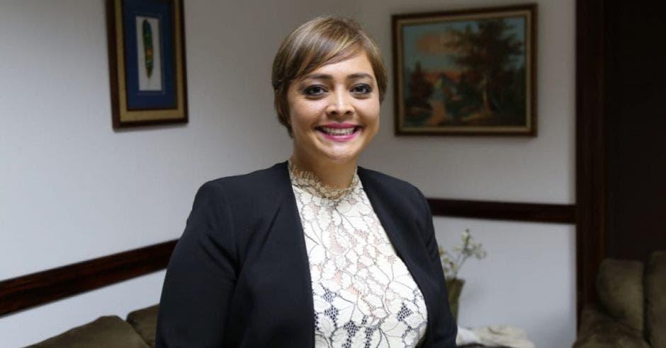 Una mujer con blaser negro y pelo corto sonriendo