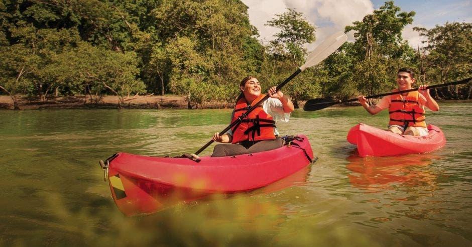 dos jóvenes cruzan un río a bordo de un kayak rojo