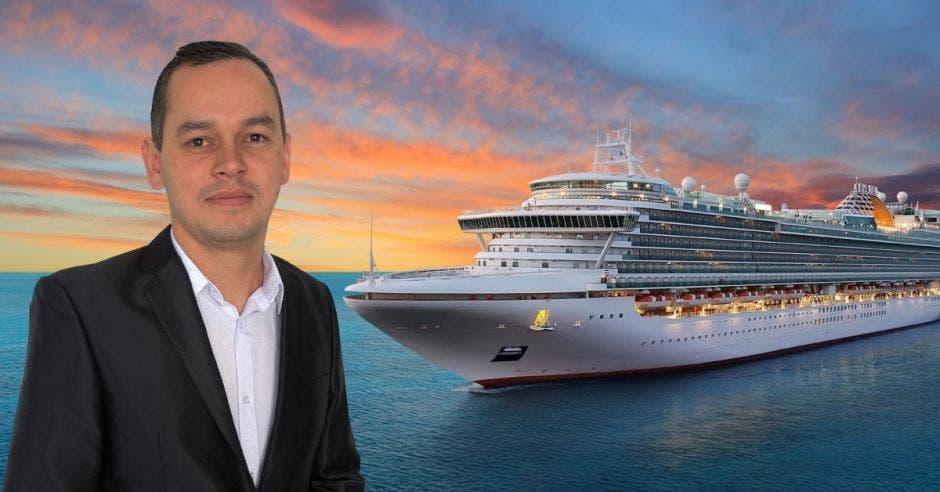 Un hombre con saco y corbata frente a la imagen de un crucero