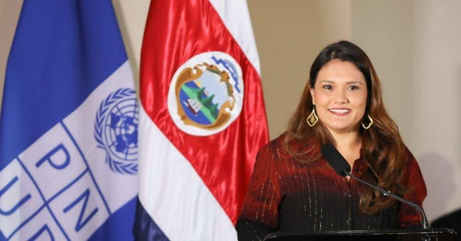 una mujer con ropa oscura junto a la bandera de Costa Rica