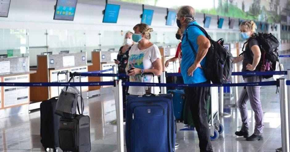 Una pareja de adultos mayores espera su turno en el counter de un aeropuerto