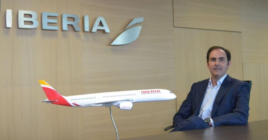 Un hombre sentado junto a un avión de Iberia a escala