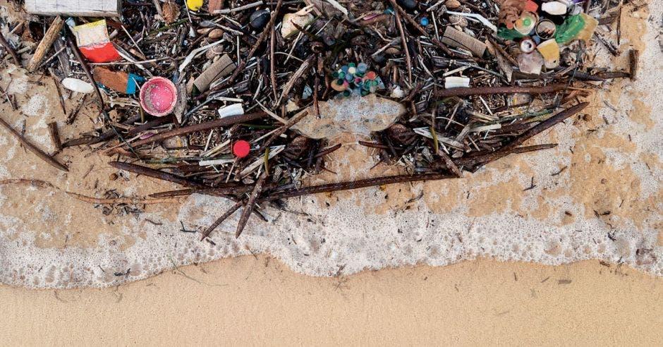 Una ola arrastrando basura en la costa