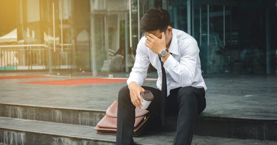Un hombre sentado en una escalera se lamenta