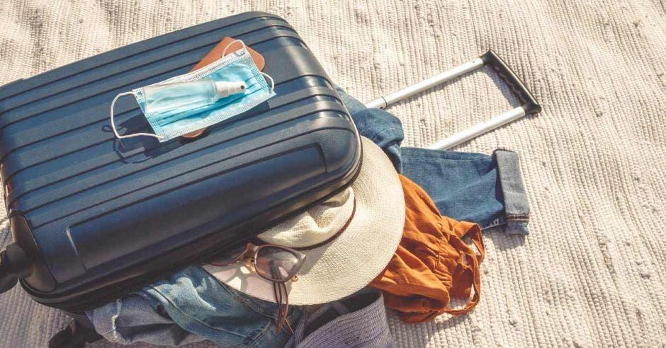 Vemos una maleta abierta con atuendos turísiticos y una mascarilla.