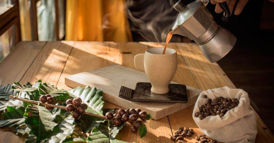 una taza de café hirviendo en una mesa de madera