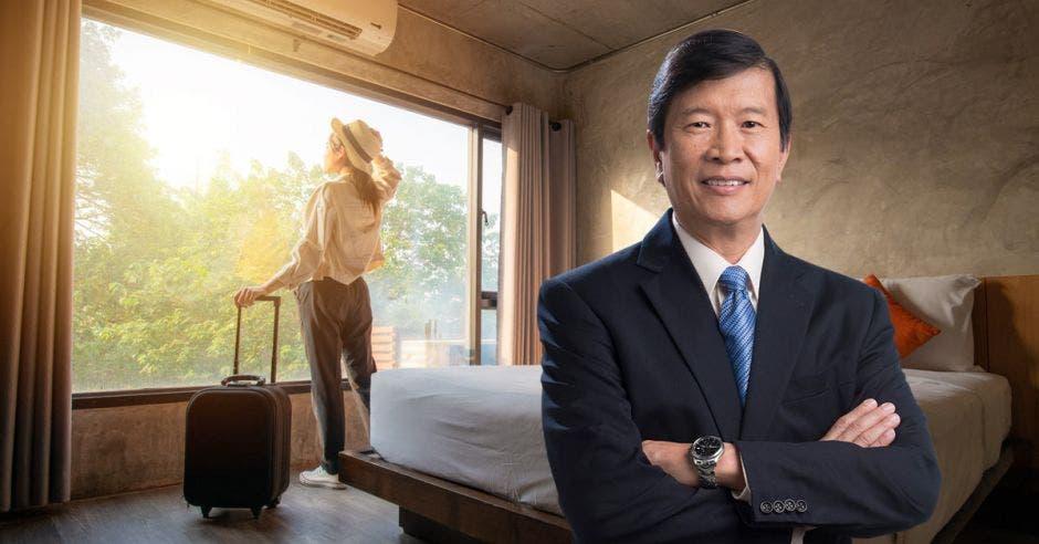 Un hombre asiático de traje y corbata azul posa junto a una habitación de hotel