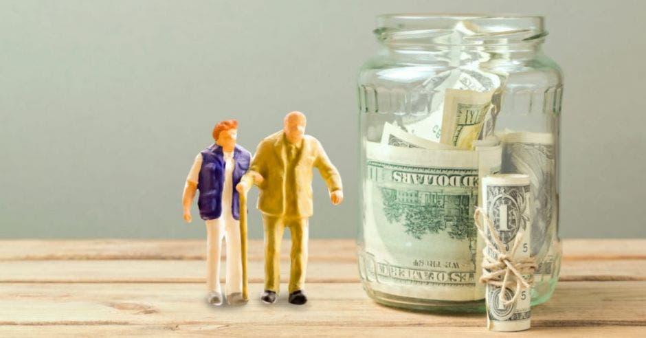 Muñecos de adultos mayores junto a jarrón con dinero
